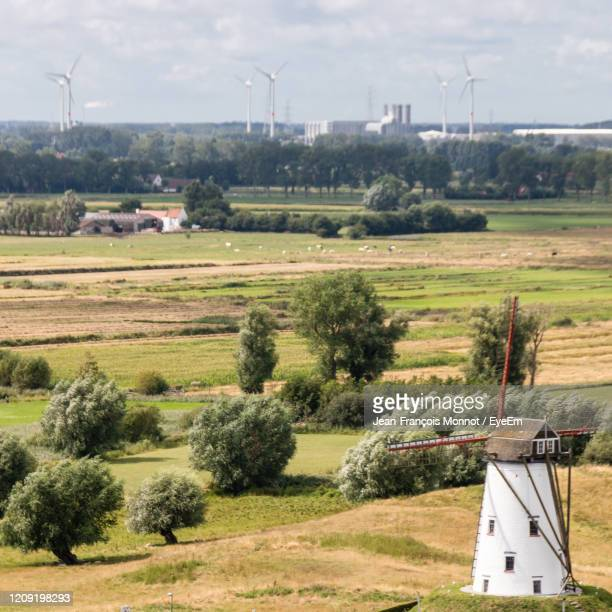 traditional windmill on field against sky - damme stock pictures, royalty-free photos & images