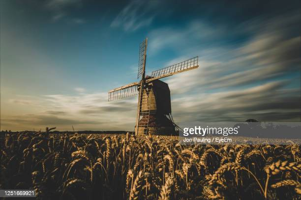 traditional windmill on field against sky - milton keynes stock pictures, royalty-free photos & images