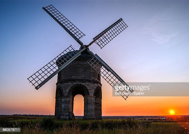 traditional windmill on grassy field against sky during sunset - old windmill stock photos and pictures