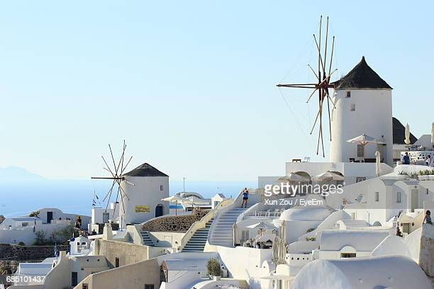 Traditional Windmills In Village At Santorini Against Clear Sky
