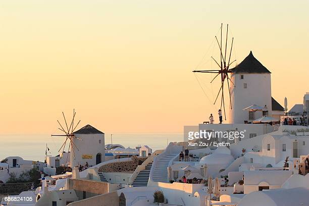 Traditional Windmills In Village At Santorini Against Clear Sky During Sunset