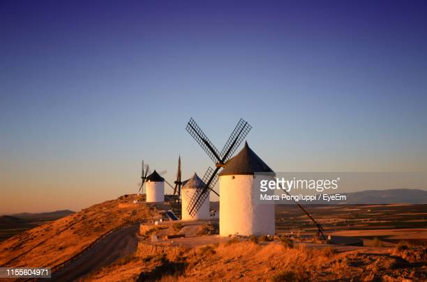 Traditional Windmills On Field Against Clear Sky