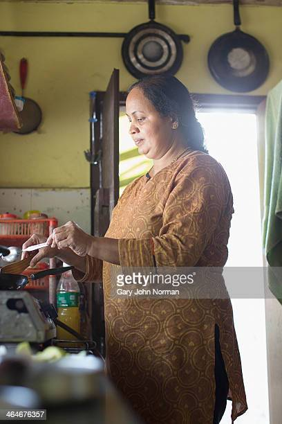 traditional woman cooking on gas stove