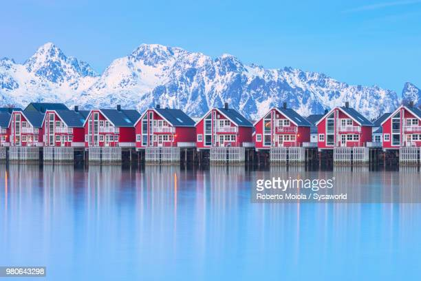 traditional wood houses called rorbu in the fishing village of svolvaer surrounded by cold sea and snowcapped mountains at dusk, lofoten islands, norway - norwegen stock-fotos und bilder
