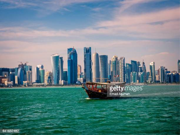 Traditional wooden boat in front of the modern Doha skyline