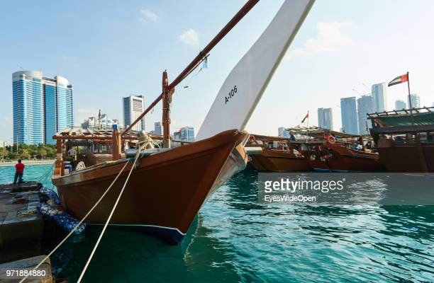 Traditional wooden boats at a harbour on Saadiyat Island are facing skyscrapers on November 27 2015 in Abu Dhabi Emirate Abu Dhabi
