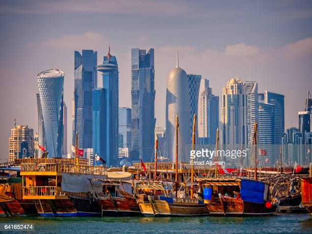 Traditional wooden boats in front of the modern Doha skyline