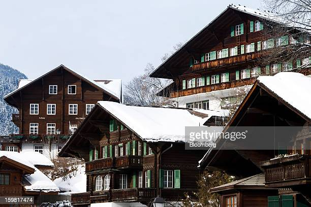 Traditional wooden Swiss chalets stand with snowcovered roofs in Gstaad Switzerland on Saturday Jan 19 2013 Options traders are pushing the cost of...