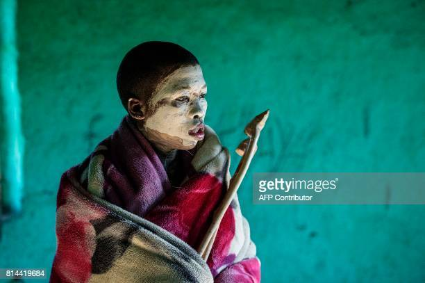 Traditional Xhosa initiate Fezikhaya Tselane, 20 years old, stands during a traditional initiation process in a rural hut on July 11, 2017 in the...