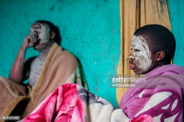 Traditional Xhosa initiates, Fezikhaya Tselane , 20 years old, and Khanyisile Mapope , 18 years old, sit down covered with blankets during a...