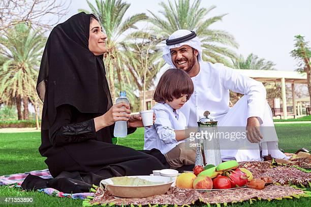 Traditional Young Arabian family having picnic at park