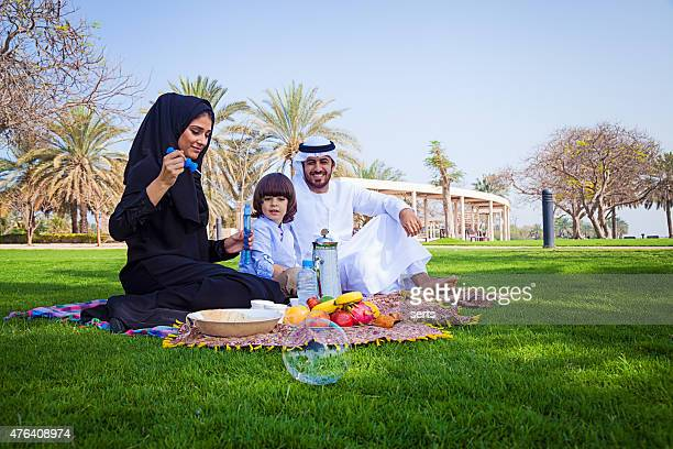 Traditional Young Arabic family having picnic at park