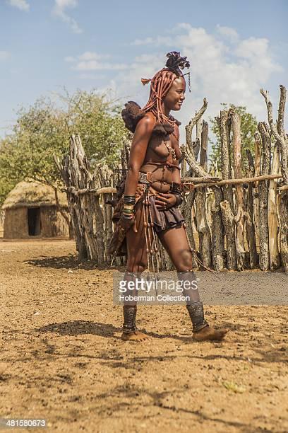Traditional Young Himba Woman Walking Towards Village