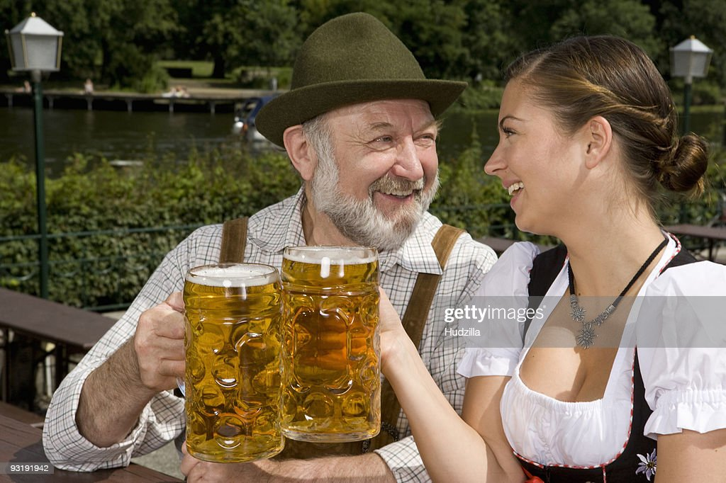 A traditionally clothed German man and woman in a beer garden toasting glasses : Stock Photo