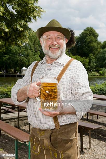 A traditionally clothed German man in a beer garden holding a beer glass