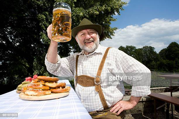 A traditionally clothed German man in a beer garden raising his beer glass in toast