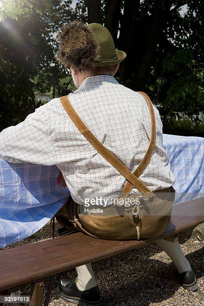 a traditionally clothed german man in a beer garden, rear view - レーダーホーゼン ストックフォトと画像