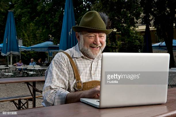 A traditionally clothed German man in a beer garden using a laptop