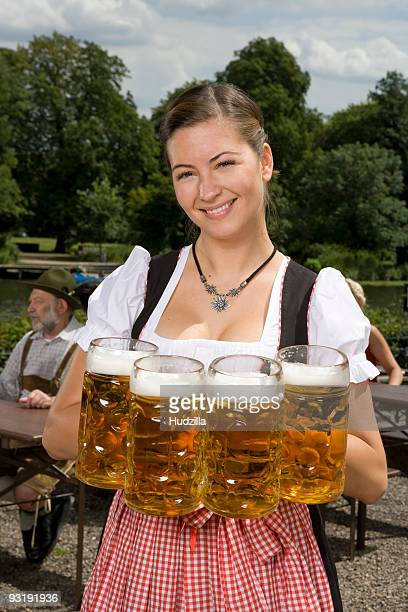 A traditionally clothed German woman serving beer in a beer garden