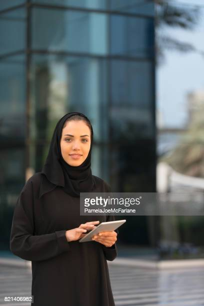Traditionally Dressed Arab Businesswoman with Computer Tablet Outside Office Building