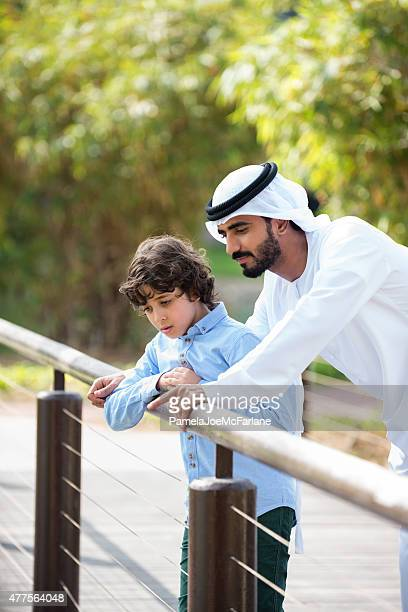 Traditionally Dressed Arab Father and Son on Bridge in Park