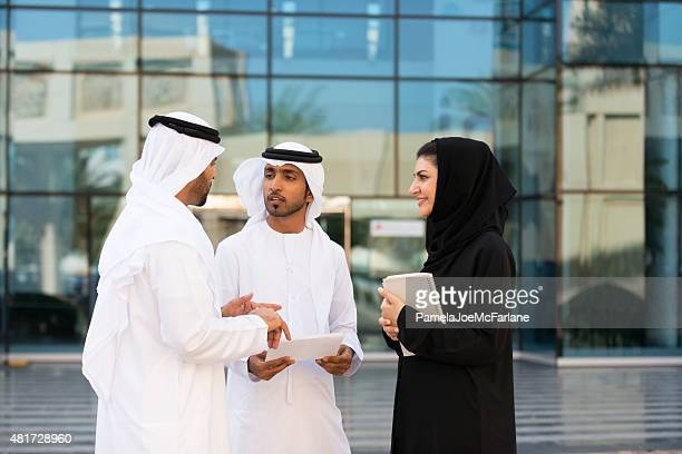 Traditionally Dressed Emirati Businessmen and Businesswoman Meeting Outside Modern Building
