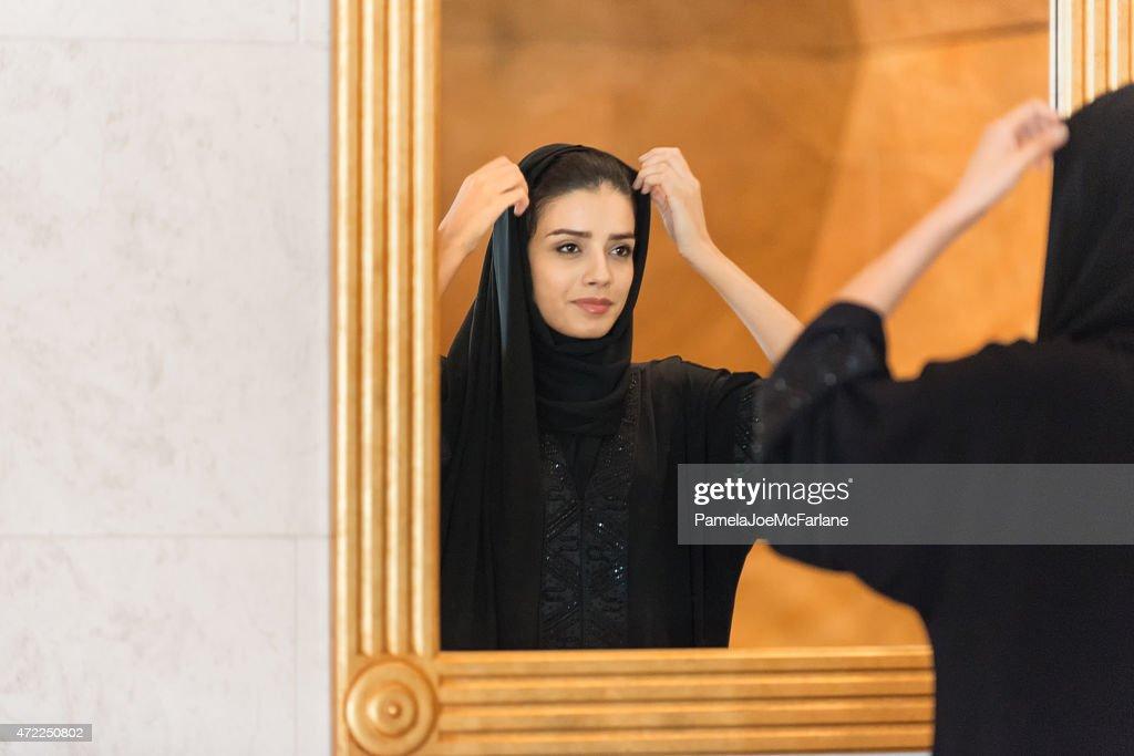 Tradizionalmente vestita Emiratino donna Regolazione specchio incorniciato in oro Hijab : Foto stock