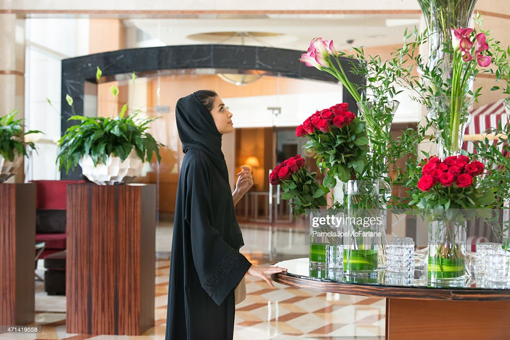 Traditionally Dressed Emirati Woman Admiring Flower Arrangements In Hotel Lobby High Res Stock Photo Getty Images