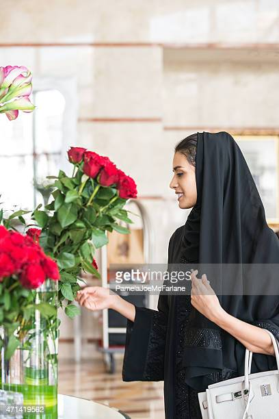 traditionally dressed emirati woman enjoying red roses in hotel lobby - red purse stock pictures, royalty-free photos & images