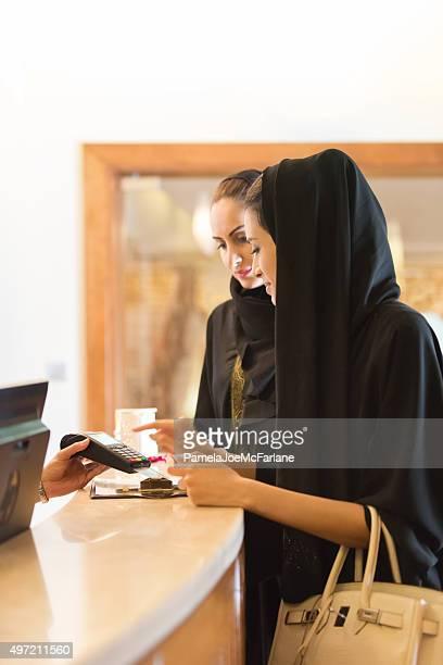 Traditionell gekleideten emiratischen Frau bezahlen mit Kreditkarte an der Theke