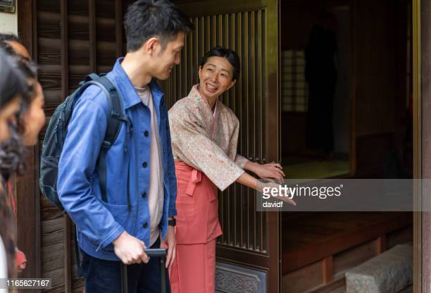 伝統的に服を着た日本人女性が旅館を訪れる人にお辞儀をする - 旅館 ストックフォトと画像