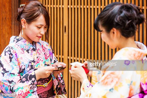 Traditionally Dressed Japanese Women in Kimonos Greet Each Other