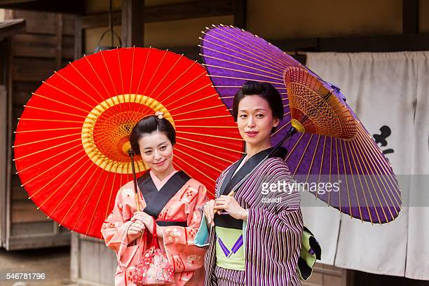 traditionally dressed japanese women in kimonos with umbrellas - geisha fotografías e imágenes de stock