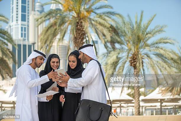 Traditionally Dressed Middle Eastern Businessman and Businesswomen Reviewing Digital Tablet