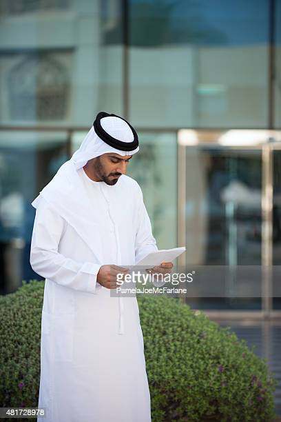 Traditionally Dressed Middle Eastern Businessman Reading Documents Outside Modern Office
