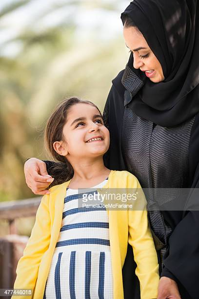 traditionally dressed middle eastern mother holding and smiling with daughter - wedding veil stockfoto's en -beelden