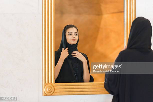 Traditionally Dressed Middle Eastern Woman Adjusting Hijab, Looking into Mirror