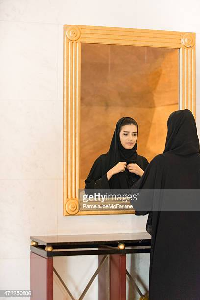 Traditionally Dressed Middle Eastern Woman Looking In Mirror, Adjusting Hijab