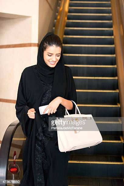 Traditionally Dressed Middle Eastern Woman Stepping off Hotel Escalator