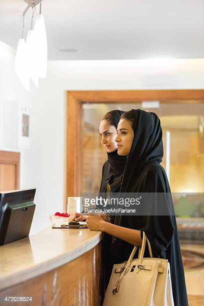 Traditionally Dressed Middle Eastern Women Checking In at Hotel Reception