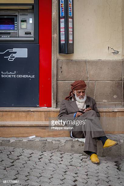 CONTENT] A traditionally dressed Muslim man with a cell phone and yellow leather babouches slippers sits next to an ATM machine in medina of Fes...