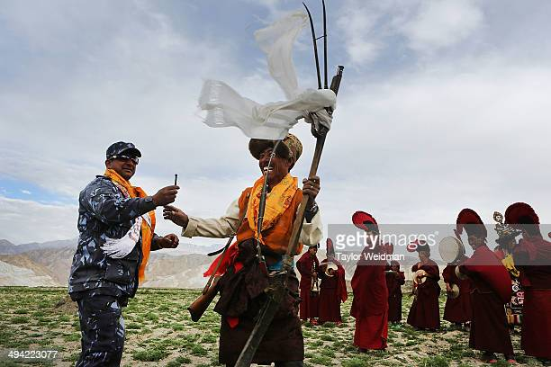 Traditionally dressed representatives of Upper Mustang's villages fire antique guns to chase demons from the city during the Tenchi Festival on May...