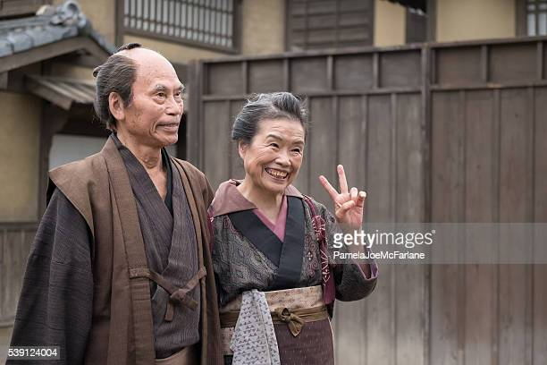 Traditionally Dressed Senior Japanese Man and Woman Giving Peace Sign