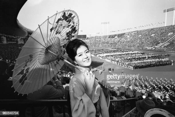 Traditionally garbed Yuko Shibayama of Tokyo watches the colorful opening ceremonies of the 18th Olympiad at the National Stadium.
