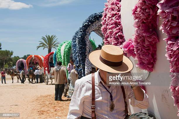 Traditions and celebrations, Pilgrimage of El Rocio, Andalucia, Spain. Pilgrims and horsemen, a pilgrim wearing flamenco clothes beside a line of...