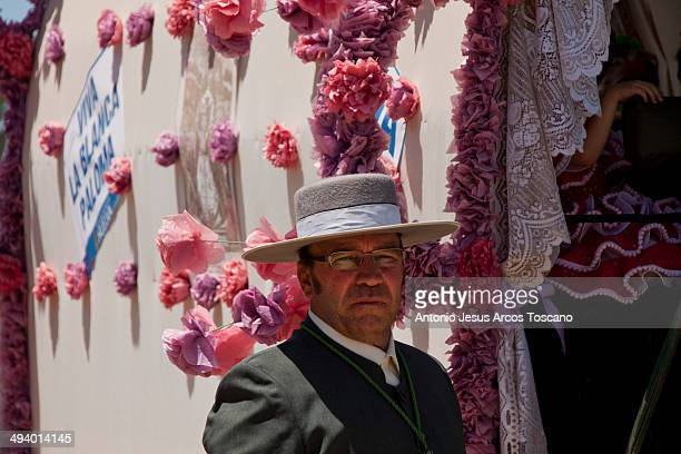 Traditions and festivals, Pilgrimage of El Rocio, Andalucia, Spain. Portrait of a pilgrim wearing flamenco clothes and hat, in front of his cart...