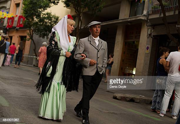 A tradtiional 'chulapos' couple walk down a street in the historic La Latina neighbourhood during the Fiestas de la Paloma on August 14 2015 in...