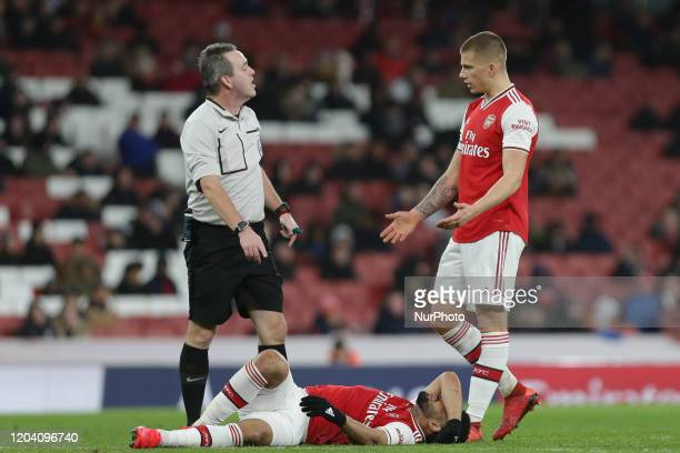Trae Coyle of Arsenal u23 down injured with the referee and Harry Clarke of Arsenal u23 during the Premier League 2 match between Arsenal Under 23...