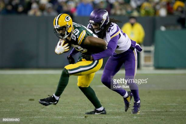 Trae Waynes of the Minnesota Vikings tackles Michael Clark of the Green Bay Packers in the fourth quarter at Lambeau Field on December 23, 2017 in...