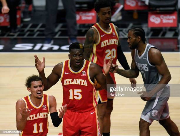 Trae Young and Clint Capela of the Atlanta Hawks react to a Hawks foul as Kawhi Leonard of the LA Clippers celebrates his basket during a 119-110...